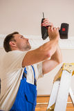Handyman using a cordless drill to the ceiling Stock Image
