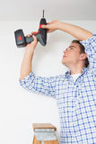 Handyman using a cordless drill to the ceiling Stock Photography