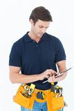 Handyman using digital table over white background Stock Image
