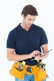 Handyman using digital table over white background Stock Image