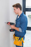 Handyman using a drill with toolbelt around waist Royalty Free Stock Image