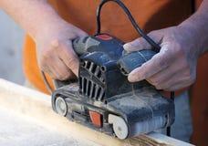 Handyman using electric sander. Stock Photo