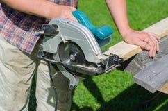 Handyman using hand-held saw Stock Photos