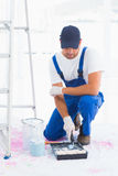 Handyman using paint roller in tray at home Stock Images