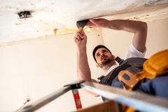 Handyman is using a putty knife. Enabling him maximized grip for scraping royalty free stock image