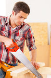Handyman using saw. Royalty Free Stock Image