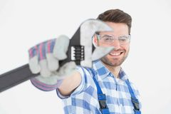 Handyman wearing protective glasses while holding wrench Royalty Free Stock Photo