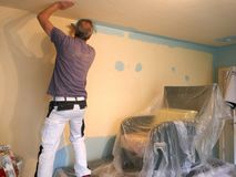 Handyman, who is stroking a wall with a painting roller. royalty free stock images