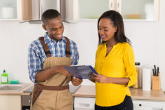 Handyman And Woman Looking At Clipboard Royalty Free Stock Photography