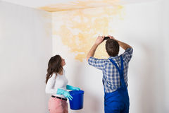 Handyman With Woman Photographing Ceiling At Home Royalty Free Stock Photo