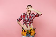 Handyman woman in shirt, denim shorts, kit tools belt full of variety useful instruments cover eyes with hand isolated stock photography