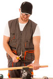 Handyman in work clothing hammering nail with hammer in home workshop. royalty free stock images