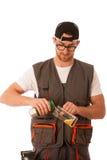 Handyman in work clothing having a break, drinkng beer. Royalty Free Stock Image