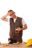 Handyman in work clothing having a break, drinkng beer. Stock Image