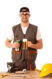 Handyman in work clothing having a break, drinkng beer. Royalty Free Stock Photo