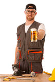 Handyman in work clothing having a break, drinkng beer. Royalty Free Stock Photography