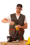 Handyman in work clothing having a break, drinkng beer. Royalty Free Stock Images