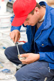 Handyman working. A young man fixing / preparing to install an electric switch - part of a series Royalty Free Stock Photo