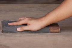 Handyman working with sandpaper on a wooden table Royalty Free Stock Image