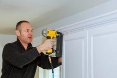 Handyman working instal brad nail gun to Crown Moulding wall cabinets framing trim royalty free stock photography