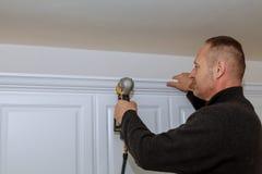 Handyman working using brad nail gun to Crown Moulding on white wall cabinets framing trim, Stock Image