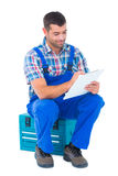 Handyman writing on clipboard while sitting on toolbox Royalty Free Stock Photography