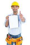 Handyman in yellow hard hat with clipboard gesturing thumbs up Royalty Free Stock Photos