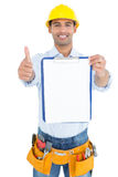 Handyman in yellow hard hat with clipboard gesturing thumbs up Stock Photos