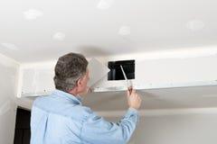 Hemförbättring leverantörman installerar drywallen Royaltyfri Bild