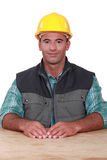 Handyman som sitts på ett skrivbord Fotografering för Bildbyråer