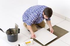 handymanhemförbättring som lägger tegelplattan Arkivfoto