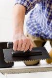 handymanhemförbättring som lägger tegelplattan Arkivbild