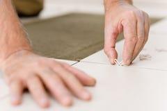 handymanhemförbättring som placerar avståndsmätaretegelplattan Royaltyfri Bild