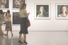 Handysuchtidee Frau in der Fotogalerie hört nicht aber mit ihrem Smartphone stockfotos