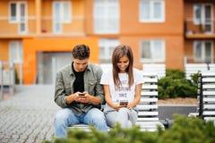 Handysuchtkonzept - verbinden Sie das Betrachten ihres Handys während auf einem Datum, das auf der Bank in der Stadtstraße sitzt Lizenzfreie Stockfotos