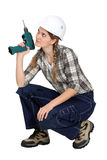 Handywoman crouching. A handywoman crouching with drill Royalty Free Stock Images