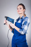 Handywoman with a drill. Woman in blue builder uniform holding an electric drill Stock Images