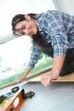 Handywoman installing wooden plank for new floor stock image