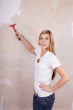 Handywoman removing wallpaper Stock Photo