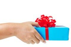 Handzeichen, das ein Geschenk eingewickelt im Blau gibt Lizenzfreie Stockfotos