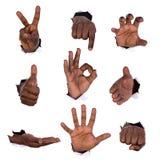 Handzeichen durch Löcher im Papier Stockbilder