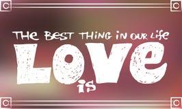 Handzeichnungstext die beste Sache in unserem Leben ist Liebe auf unscharfem rosa Hintergrund Lizenzfreie Stockfotografie