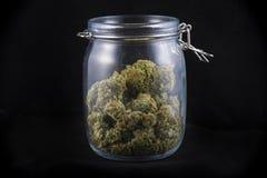 Hanfknospe in Glasgefäße lokalisiert auf schwarz- medizinischem marijua Lizenzfreies Stockfoto