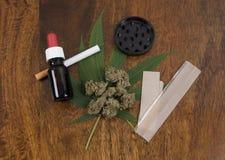 Hanfsativaunkrautblatt- und -blumenknospen auf hölzernem Hintergrund mit Schleifer, THC-Öl und großem rauchendem Papier stockfotos