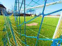 Hang bended blue yellow soccer nets, soccer football net. Grass on football playground in the background Stock Photos