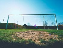 Hang bended blue yellow soccer nets, soccer football net. Grass on football playground in the background Royalty Free Stock Photos