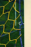 Hang bended blue yellow soccer nets, soccer football net. Plastic grass and white painted line on football play Royalty Free Stock Photo
