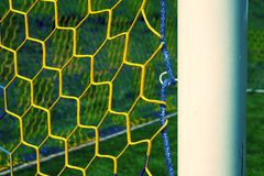 Hang bended blue yellow soccer nets, soccer football net. Plastic grass and white painted line on football play Stock Image