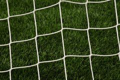 Hang bended soccer nets, soccer football net. Grass on football playground Royalty Free Stock Photography