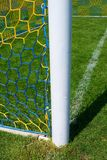 Hang bended soccer nets, soccer football net. Grass on football playground in the background Royalty Free Stock Images